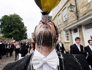 An Oxford student has a quick tipple, wearing 'sub fusc'